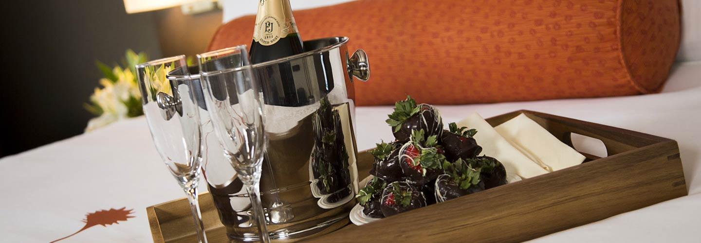 A bottle of champagne and two glasses sitting on a hotel guest bed with chocolate covered strawberries